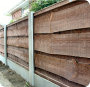 Concrete fence posts and bases with close board (vertilap or vertical lap or feather edge) fence panels.